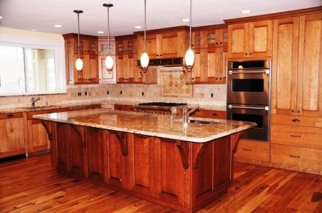 Custom kitchen cabinets and kitchen island made from cherry wood. Custom designed, built and installed by Legacy Mill & Cabinet.